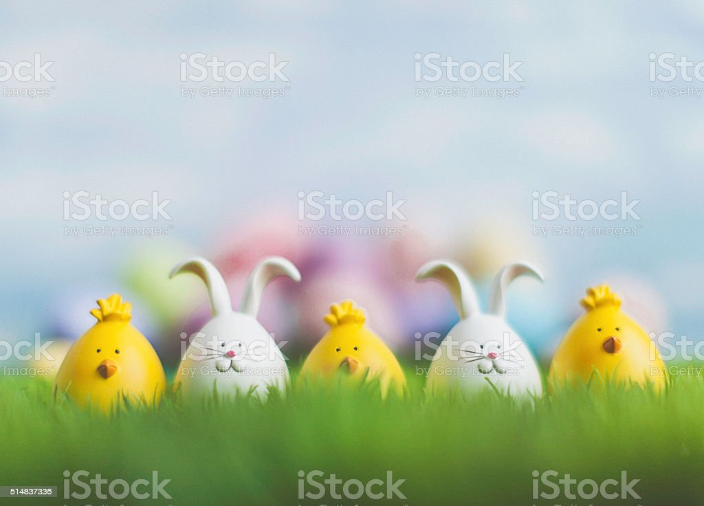 Little Easter critters sitting in grass with Easter egg background stock photo