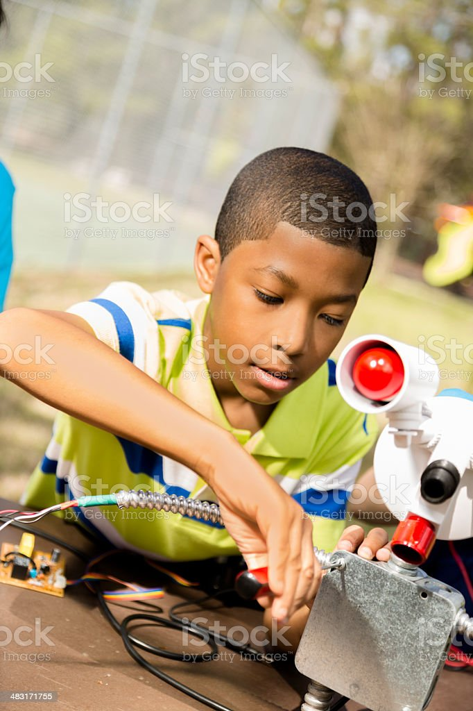 Little engineer!  Elementary child works on 'robot' he created. stock photo