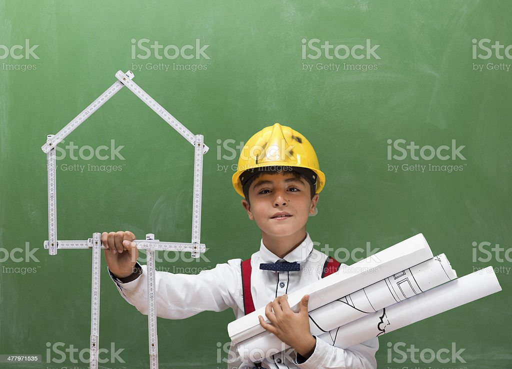 Little engineer with helmet and blue prints before blackboard royalty-free stock photo