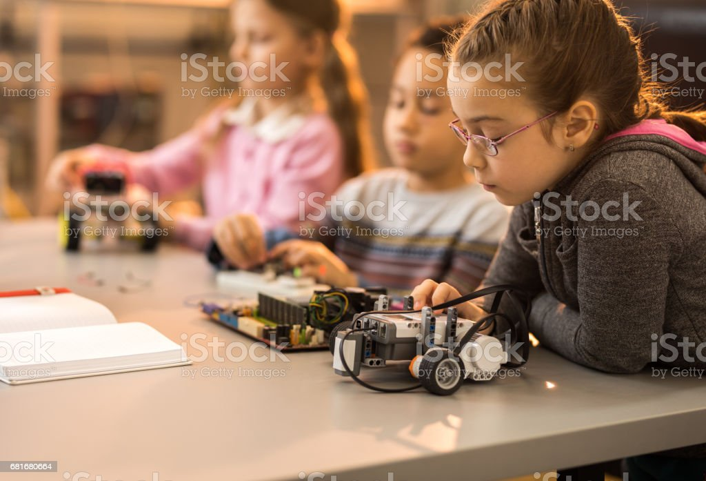 Little engineer working on innovative robots with her friends in laboratory. stock photo