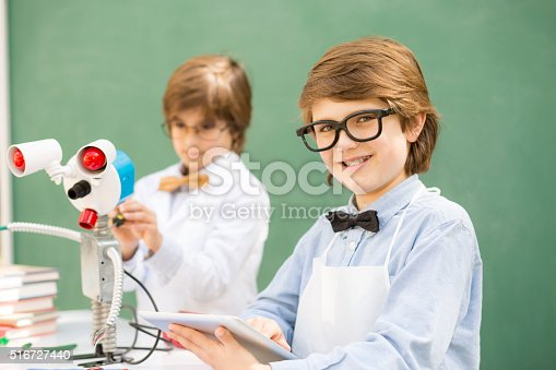 istock Little engineers! Elementary-age children collaborate on 'robot' creation. 516727440