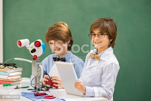 istock Little engineers! Elementary-age children collaborate on 'robot' creation. 516820300