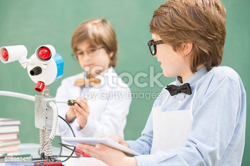 istock Little engineers! Elementary-age children collaborate on 'robot' creation. 528982486