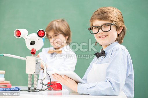 istock Little engineers! Elementary-age children collaborate on 'robot' creation. 530823400