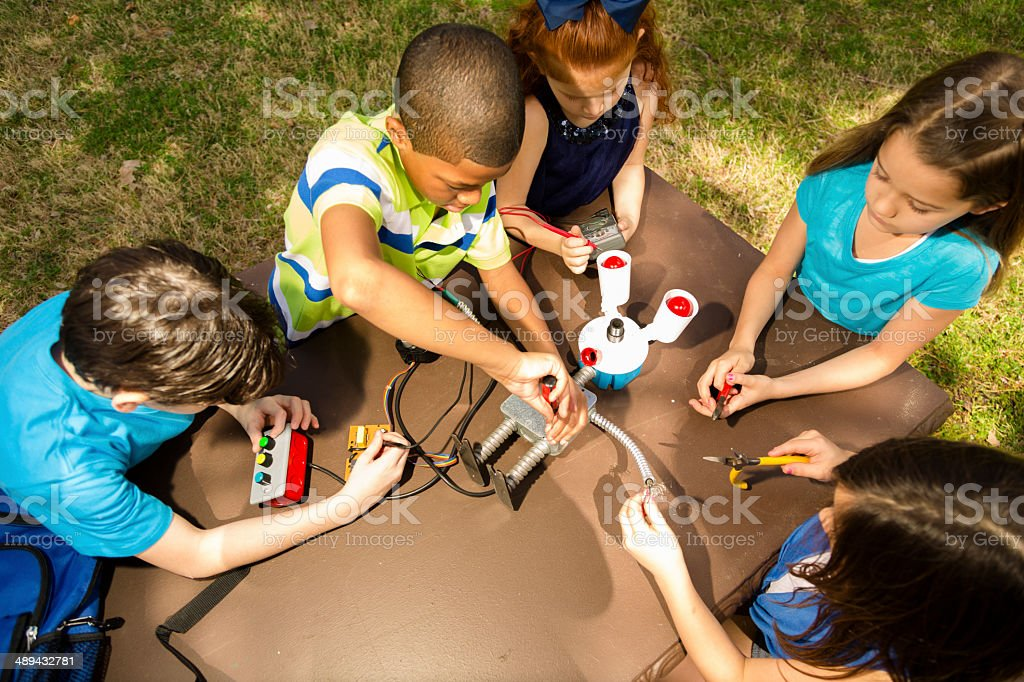 Little engineers!  Ethnic elementary children collaborate on 'robot' they created. stock photo