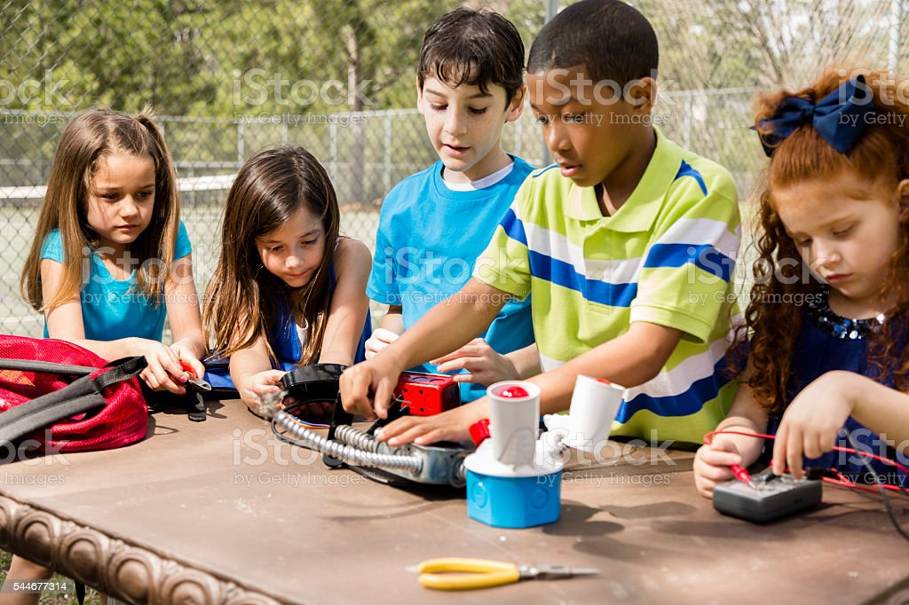 Little engineers! Multi-ethnic elementary children collaborate on 'robot' creation. stock photo