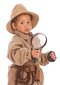 Adorable toddler dressed in Khaki and holding a magnifying glass.  A whip hanging from his belt. Isolated on white.
