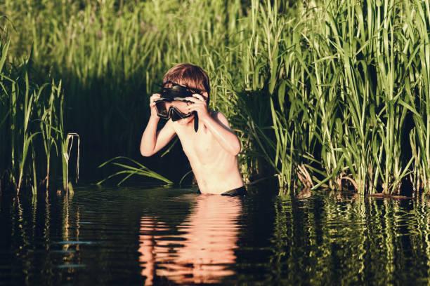 Kleiner Forscher. Das Kind schaut in das Wasser des Flusses. – Foto
