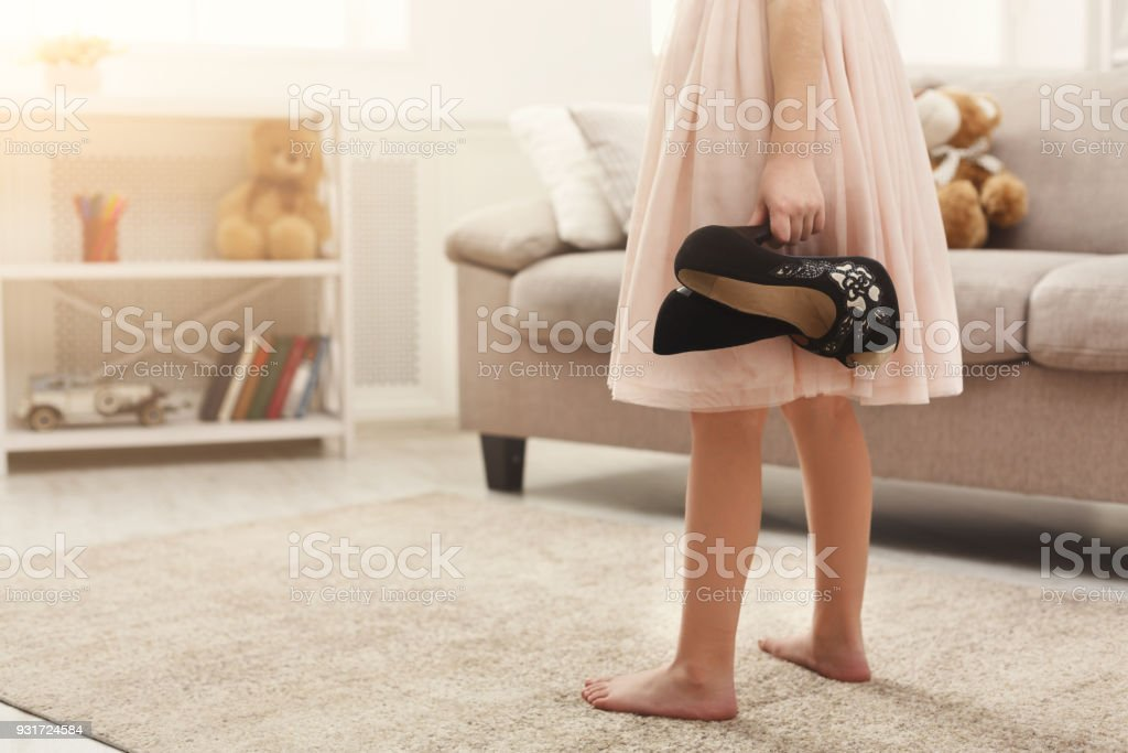 Little fashionista trying on her mom`s shoes - foto stock