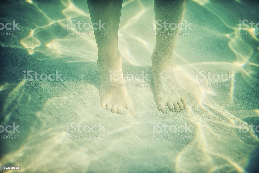 Little feet underwater on sea bed stock photo