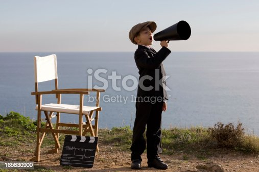 Photo of little boy in full length standing and shouting on old fashioned megaphone in outdoor.A director chair and film slate is seen just close to him.He is wearing a flat cap and a black suit.Sea is seen on the background.The image was shot in daylight with a full frame DSLR camera.