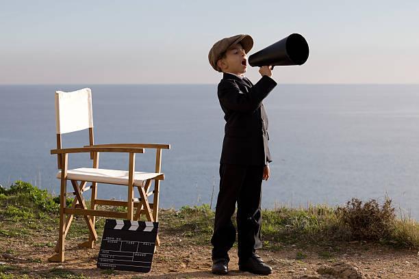 little film director rufen auf megafon in outdoor-set - klappe hut stock-fotos und bilder