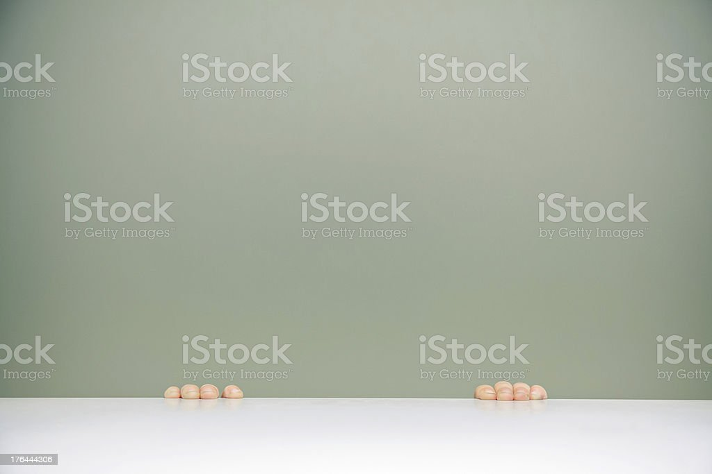 Little fingers grabbing a table stock photo