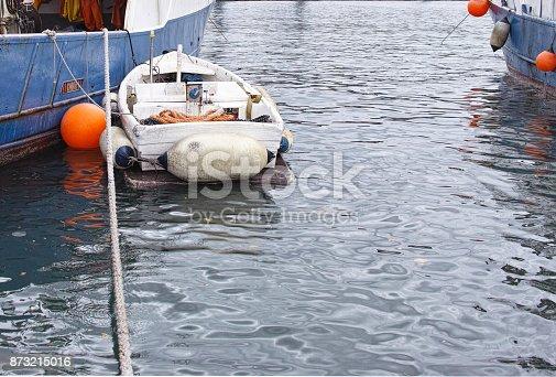 little fishing boat moore alongside a big industrial fishing boat in italy