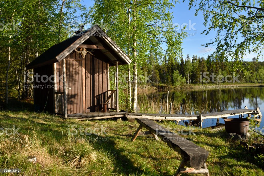Little fishing cottage att the lake shore surrounded by birch trees stock photo