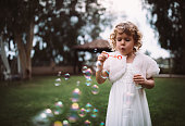 Little bridesmaid in white dress celebrating at wedding ceremony and blowing bubbles in garden