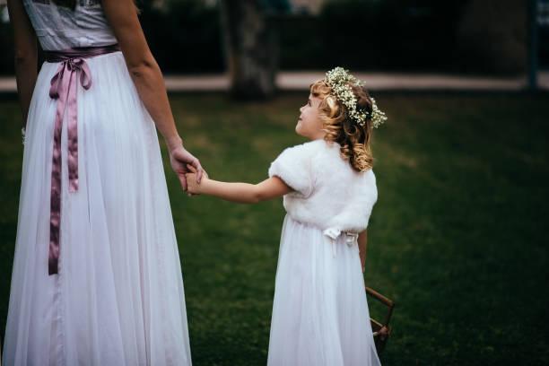 kleine blume mädchen mit blumenkorb, hand in hand mit braut - mütterbrautkleider stock-fotos und bilder