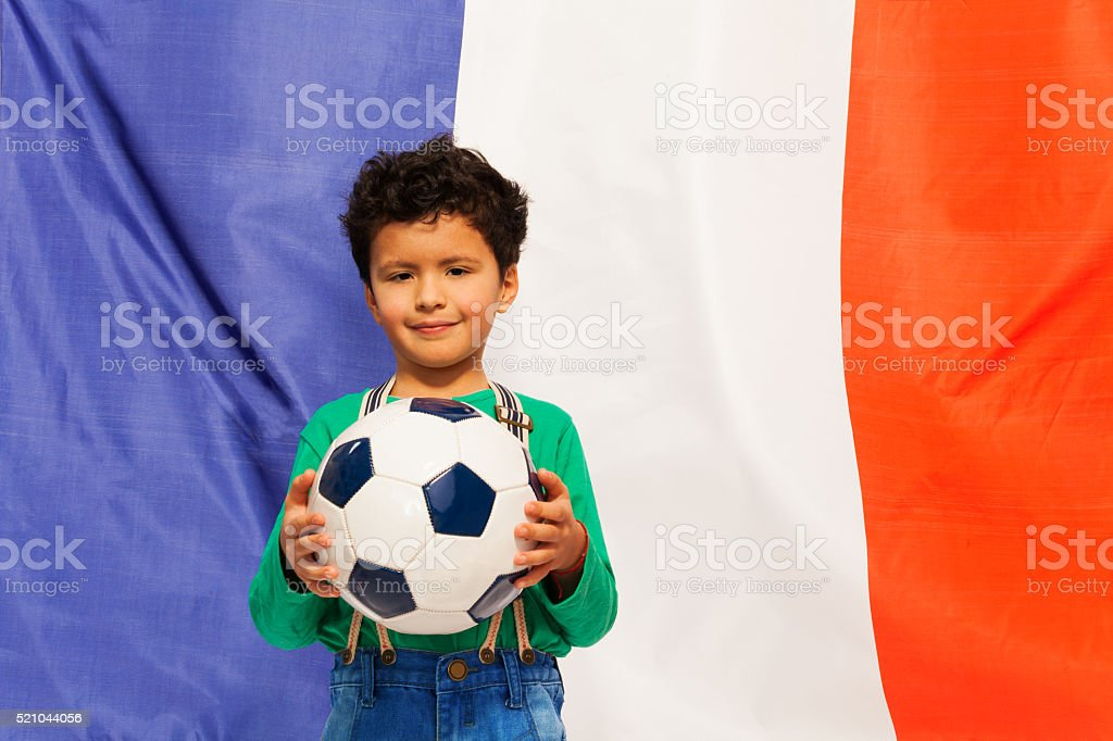 Little football fan with ball against French flag stock photo