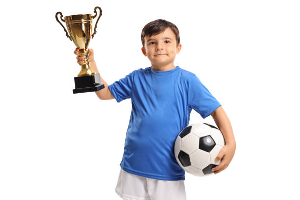 Little footballer holding a golden trophy stock photo