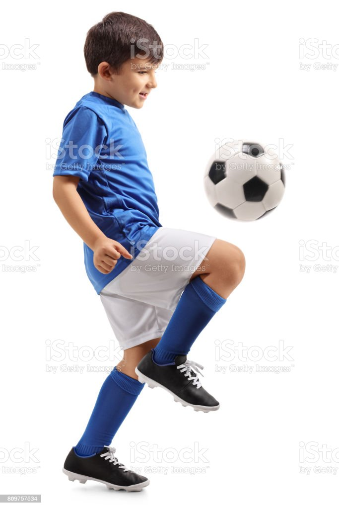 Little footballer juggling a football stock photo