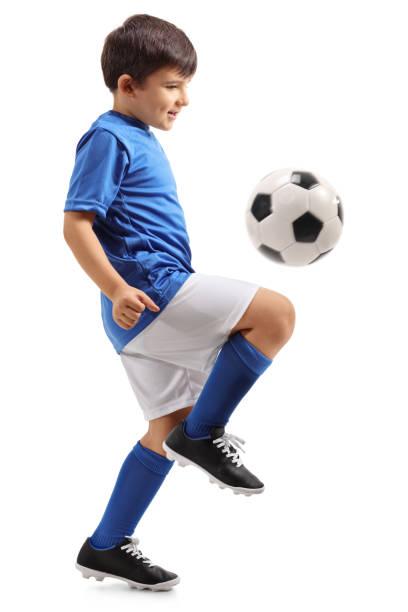 Little footballer juggling a football stock photo