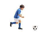 Full length profile shot of a little footballer running towards a football isolated on white background