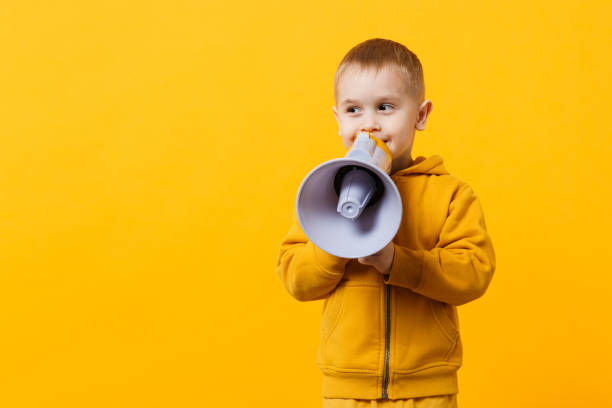 Little fun kid boy 3-4 years old in yellow clothes holding, speaking in electronic megaphone isolated on orange wall background, children studio portrait. People childhood concept. Mock up copy space. stock photo