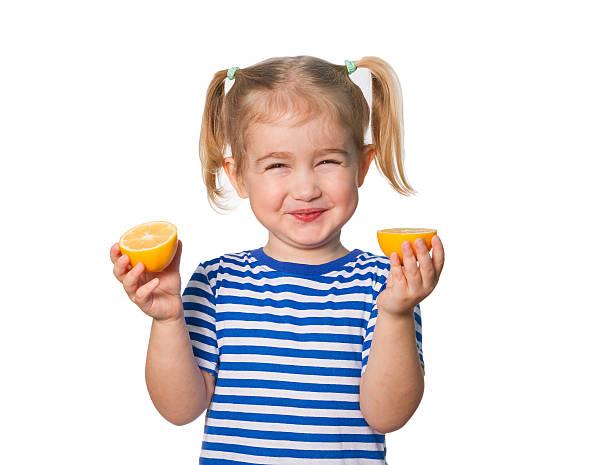 poco chica divertida mantiene limones - ácido fotografías e imágenes de stock