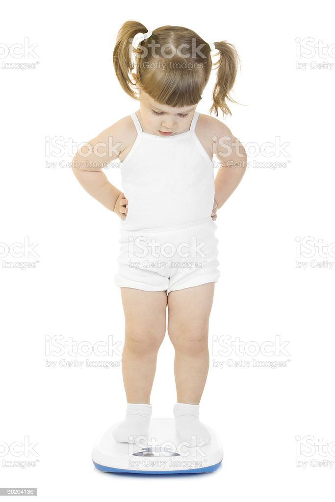 Little funny girl stand on scales stock photo