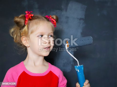 657926276 istock photo Little funny smiling girl paint the wall with magnetic paint. 949834336