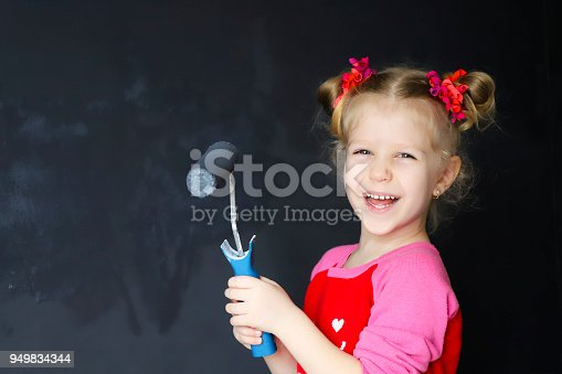 657926276 istock photo Little funny smiling girl paint the wall with magnetic paint. 949834344