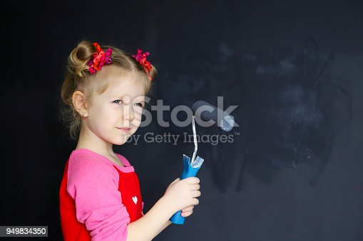 657926276 istock photo Little funny smiling girl paint the wall with magnetic paint. 949834350