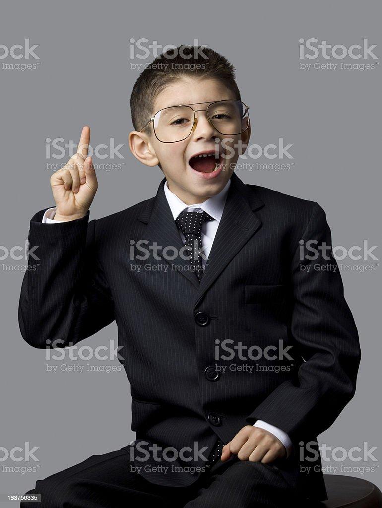 Little genius boy holding finger to speak royalty-free stock photo