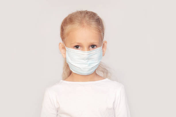 Little girl a child of European type of appearance in a medical mask on an isolated background stock photo