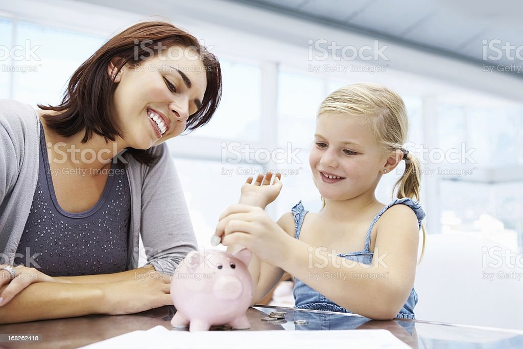 Little girl adding money to piggy bank stock photo