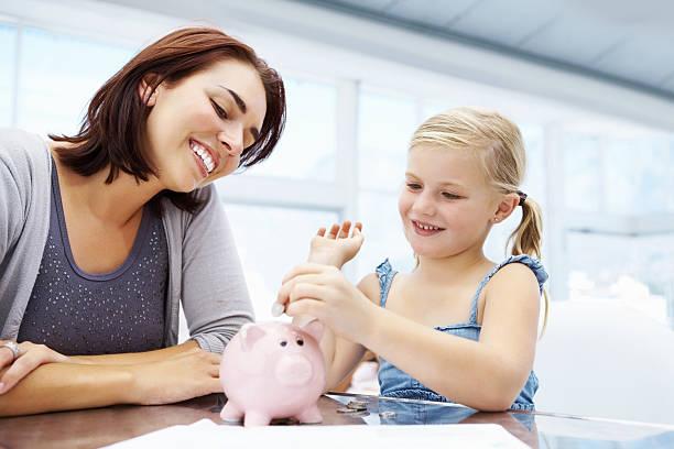 Niedliche kleine Mädchen putting Geld im Sparschwein – Foto
