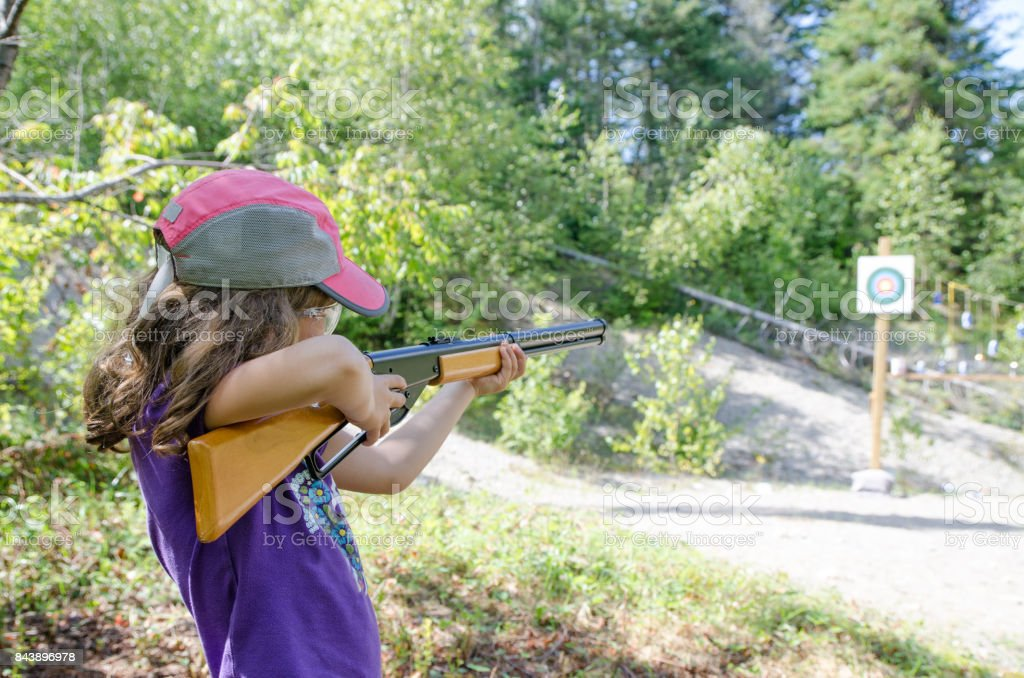 Little girl aiming at target with rifle during outdoors summer day vacations stock photo