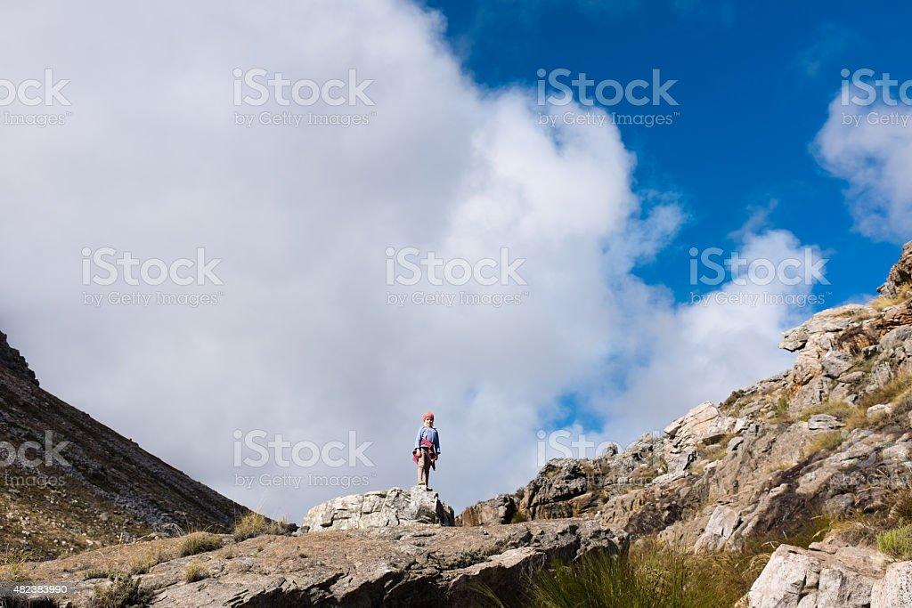 Little girl all alone on mountain peak in wilderness stock photo