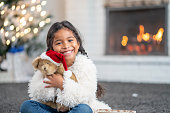 A beautiful young girl of african descent smiles into the camera in this Christmas portrait. She is cuddling a bear that is wearing a santa hat.