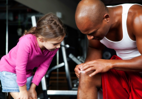 istock Little Girl and Athletic Man Putting on Band-Aid 182150947