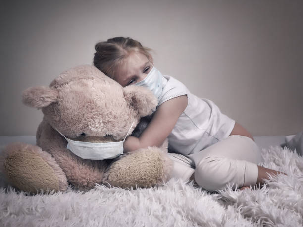 Little girl and big plush bear in medical masks. The concept of childhood diseases, empathy, support and help sick children stock photo