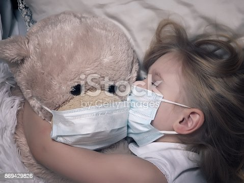 istock Little girl and big plush bear sleep in medical masks. The concept of childhood diseases, empathy, support and help sick children 869429826