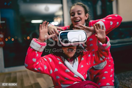 1019302738istockphoto Little Girl and Bigger Sister Having Fun with Virtual Reality Simulator and Gesturing 828160904
