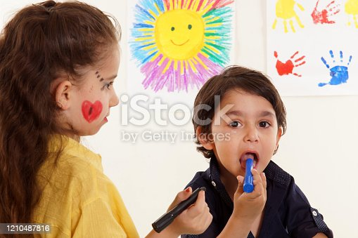 678159134 istock photo Little girl and boy are doing paint. Boy puts crayons in his mouth. 1210487816
