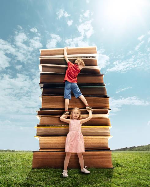kleine mädchen und junge klettern auf dem turm aus großen büchern - flyer inspiration stock-fotos und bilder