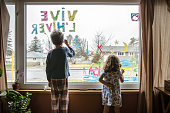 Little girl and boy coloring on the living room window a winter ambiance to be seen from exterior