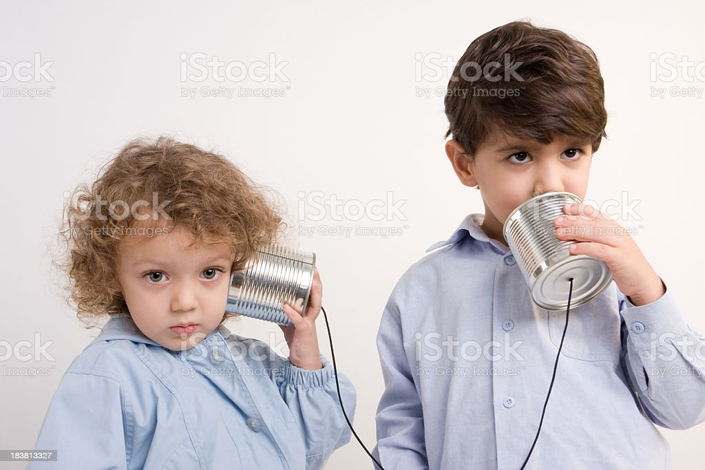 Little Girl And Boy Communicating Via Tin Can Phone stock photo