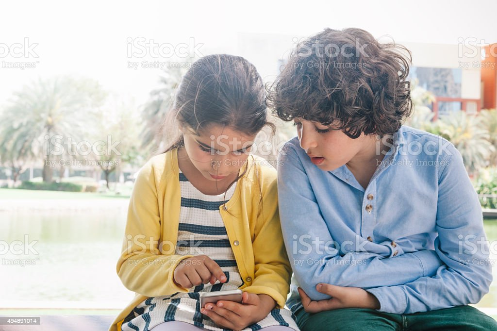 Little girl and boy enjoying smartphone at park stock photo