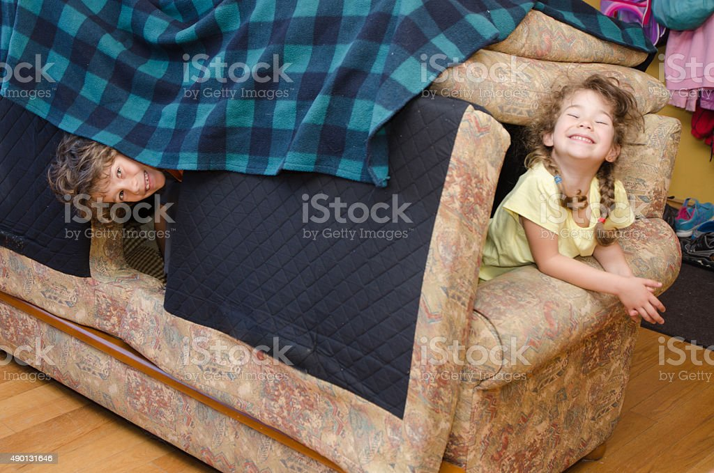 Little girl and boy peeking out from sofa house stock photo