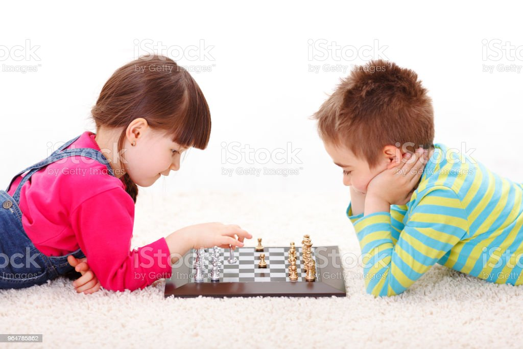 Little girl and boy playing chess royalty-free stock photo